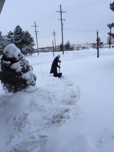 Tirando a neve da frente da garagem.